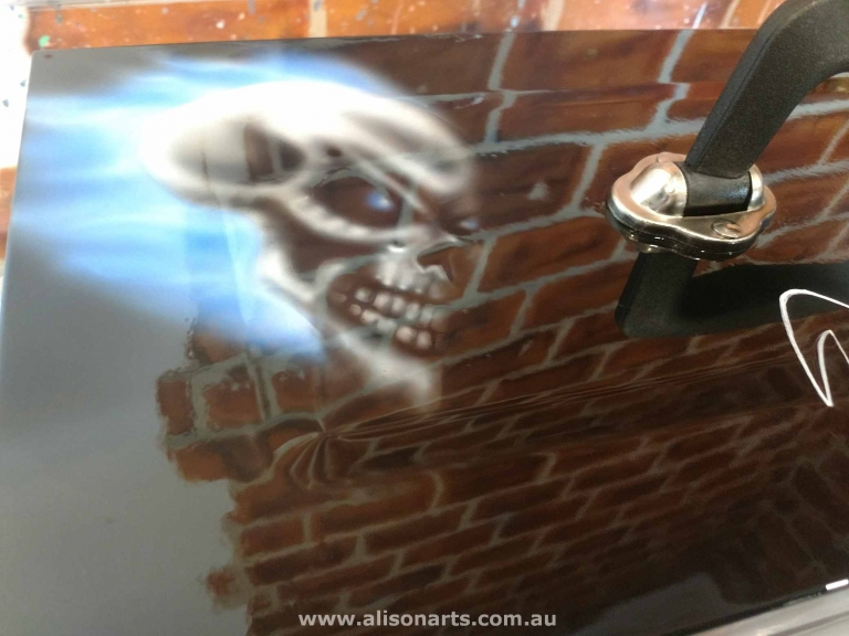 Evil skull airbrushed to toolbox lid